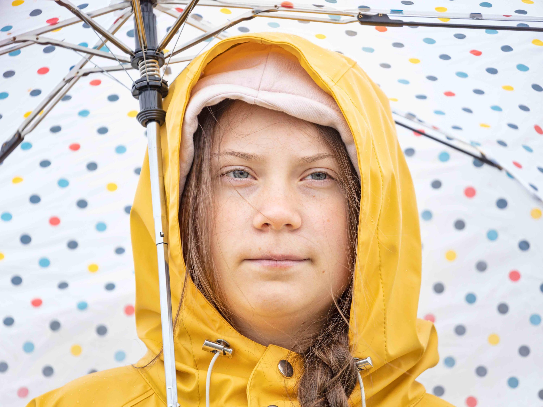 Greta Thunberg in a yellow mac holding umbrella