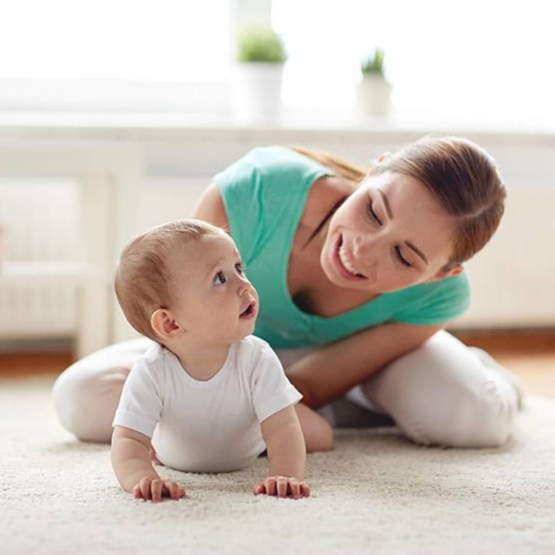 Mom encouraging baby to crawl