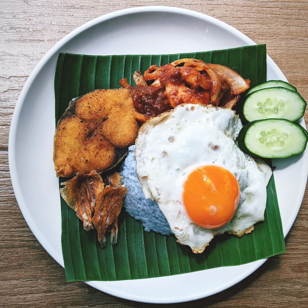 blue pea nasi lemak with all the frills - sambal prawns, fried fish, crispy salted fish, sunny side up and cucumbers. i added blue butterfly pea flowers to the rice for the pretty factor. so delicious ✨  recipes for nasi lemak and sambal prawns from @nyonyacooking