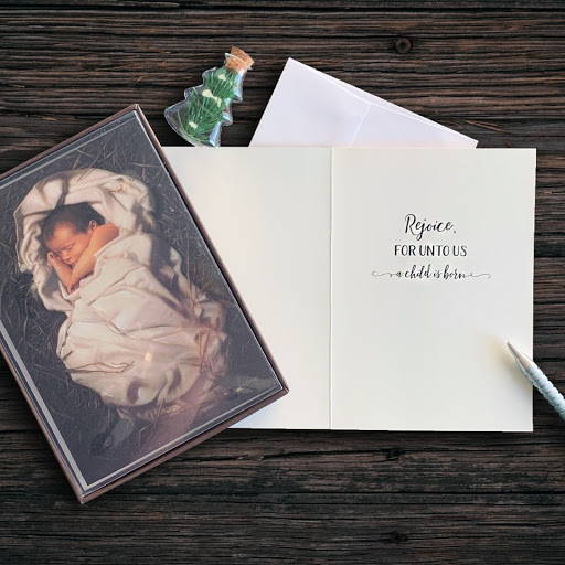 A display of Simon Dewey LDS art Christmas cards featuring the infant Jesus Christ.