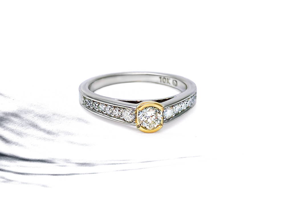White gold semi eternity with yellow gold and diamond center.