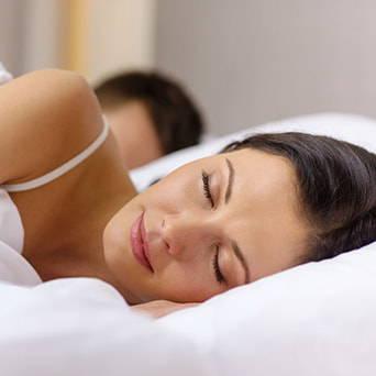 Frau schläft auf ergonomischem Kopfkissen