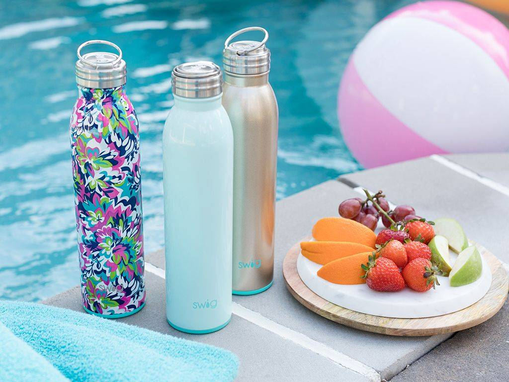 three stainless steel water bottles by a pool