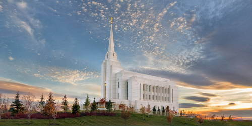 Panoramic Rexburg temple picture against a blue and orange sky.
