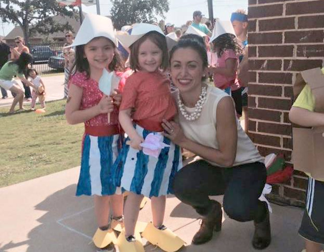 Woman poses with two young Primrose students dressed up for the parade of cultures event