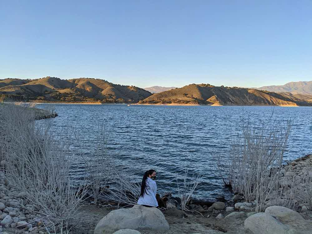 Woman sitting on a large rock overlooking Lake Cachuma in Santa Ynez Valley