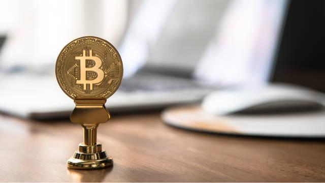 En Bitcoin-mønt, som står på et bord