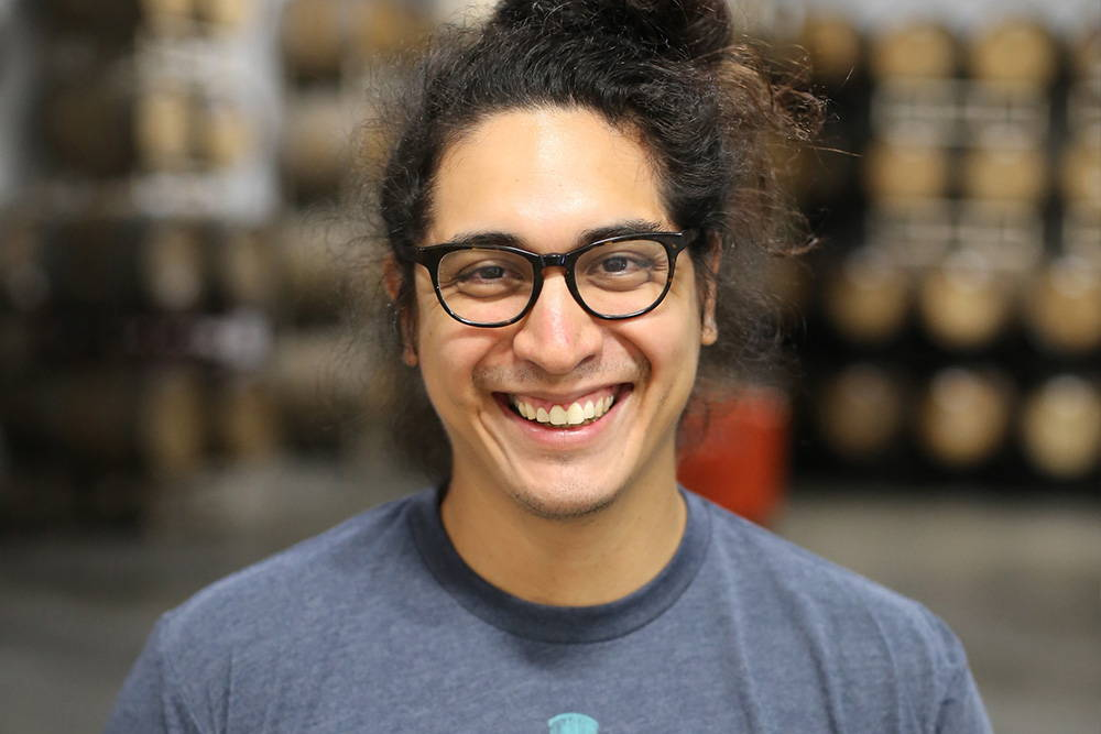 Cesar is smiling at the camera with black frame glasses from inside the Smog City sour side barrel room.