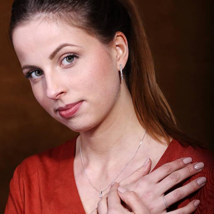 Une jeune femme avec une chemise rouge porte un collier avec un petit diamant en pendentif. Ses mains sont croisées et posées sur sa poitrine pour dévoiler la délicate bague sertie d'un pavé de diamants qu'elle porte sur son doigt.