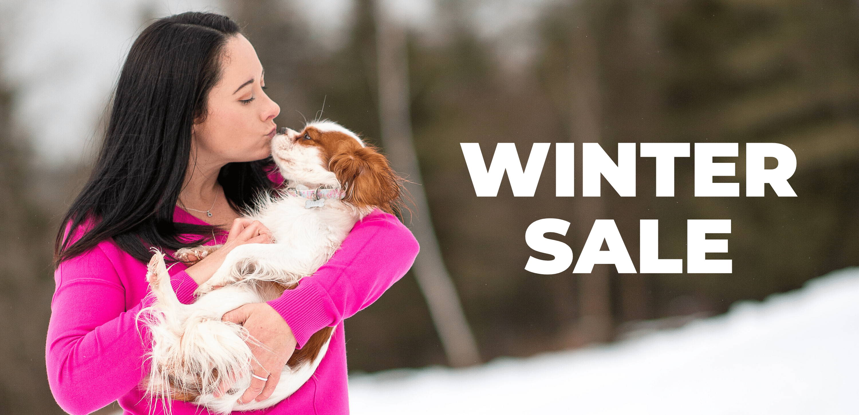 Woman in pink long sleeve shirt holding dog in C4 collar
