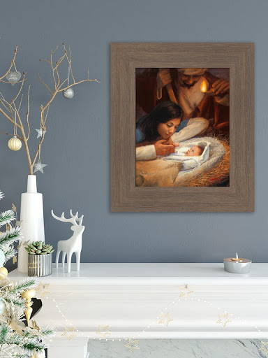 Nativity painting placed on the wall above a mantle, next to a candle and other Christmas décor.