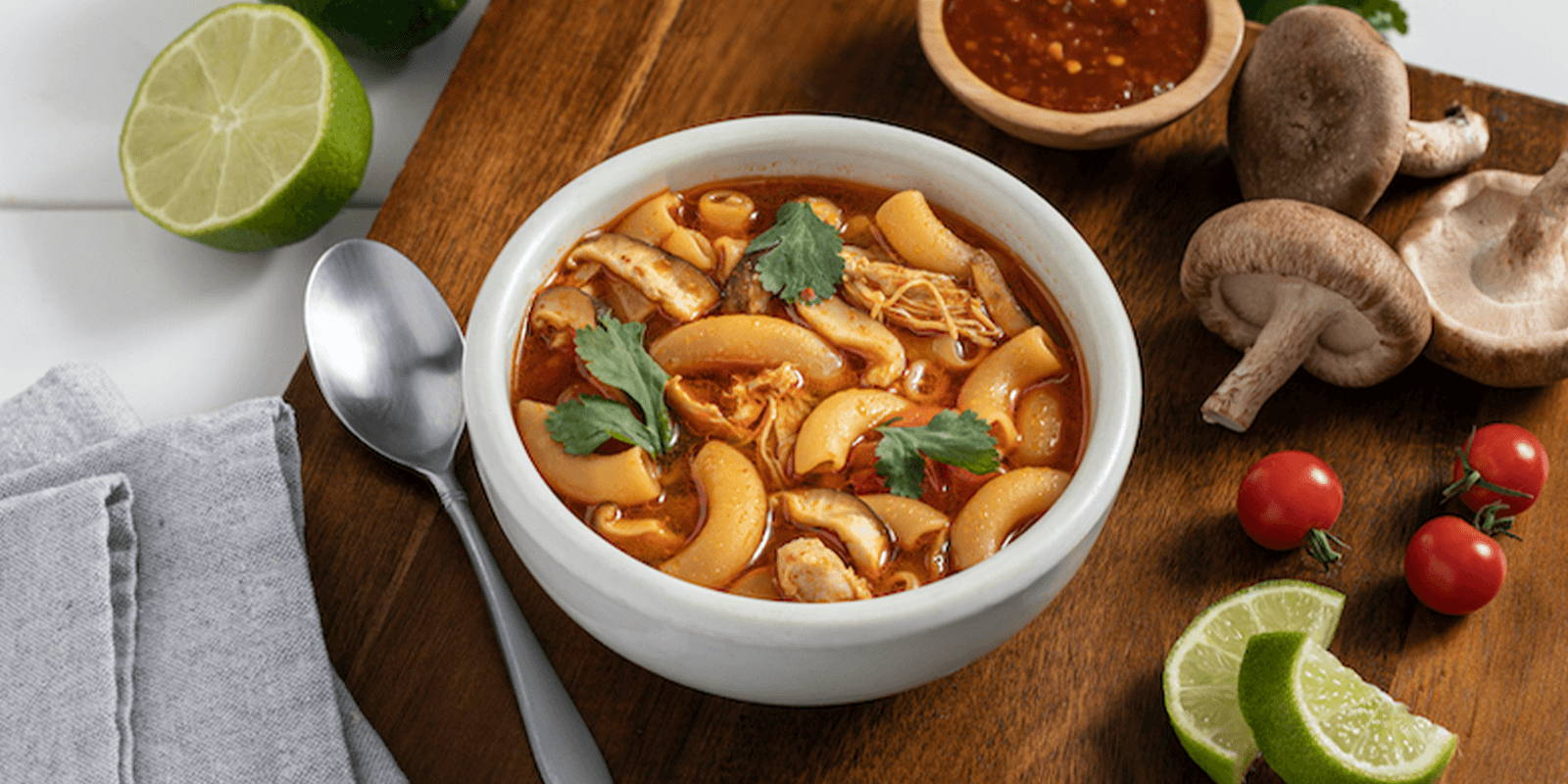 A bowl of Tom Yum-style soup made with ZENB Elbows Pasta garnished with cilantro, sambal, and lime.