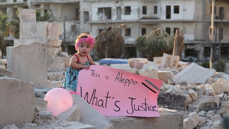 A toddler standing in the ruins of a building holding a sign which reads 'This is Aleppo. What's Justice'.