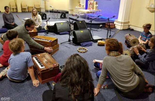 Families learning musical instruments in Melbourne Ashram Hall