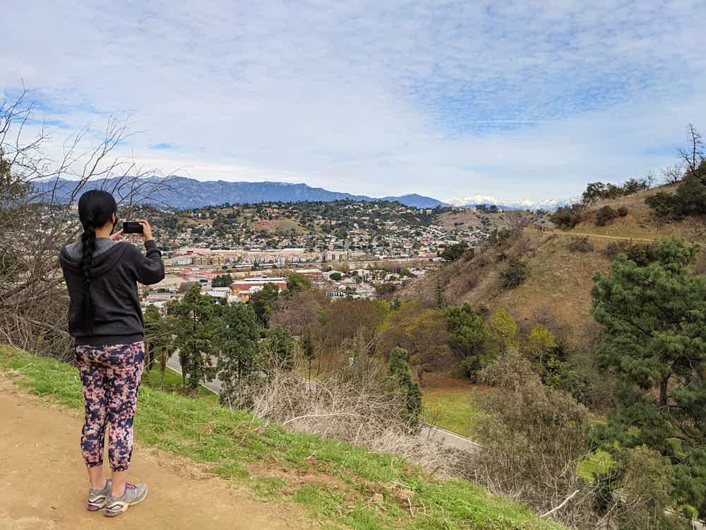 Woman taking a phone photo of the scenery at Elysian Park in Los Angeles