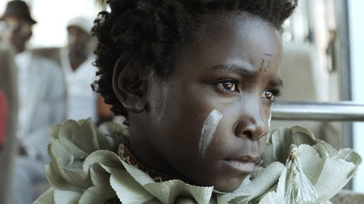 A girl with white paint on her face looks to the right.