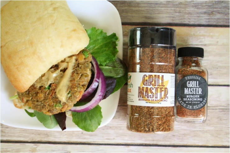 A plate with a lentil and chickpea burger next to two bottles of FreshJax Organic Grill Master  Burger Blend.