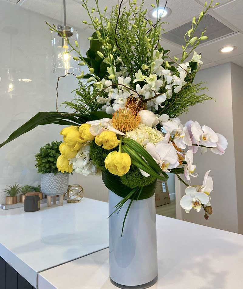 Arrangement of white, green and yellow flowers in a white vase placed on a table