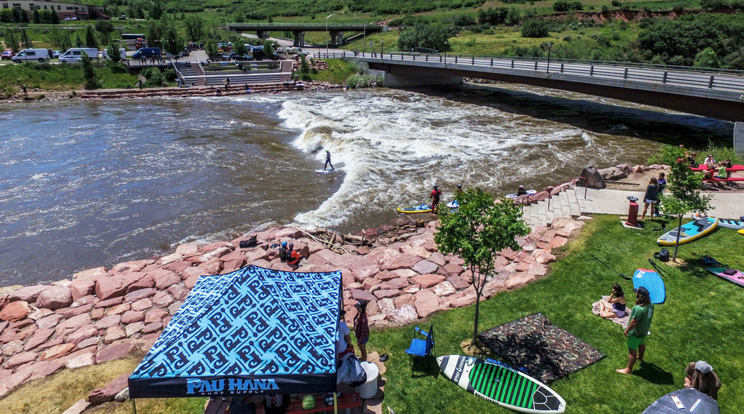 Pau hana crew tents and set up at the games in Colorado with river racing carve sup in the photo