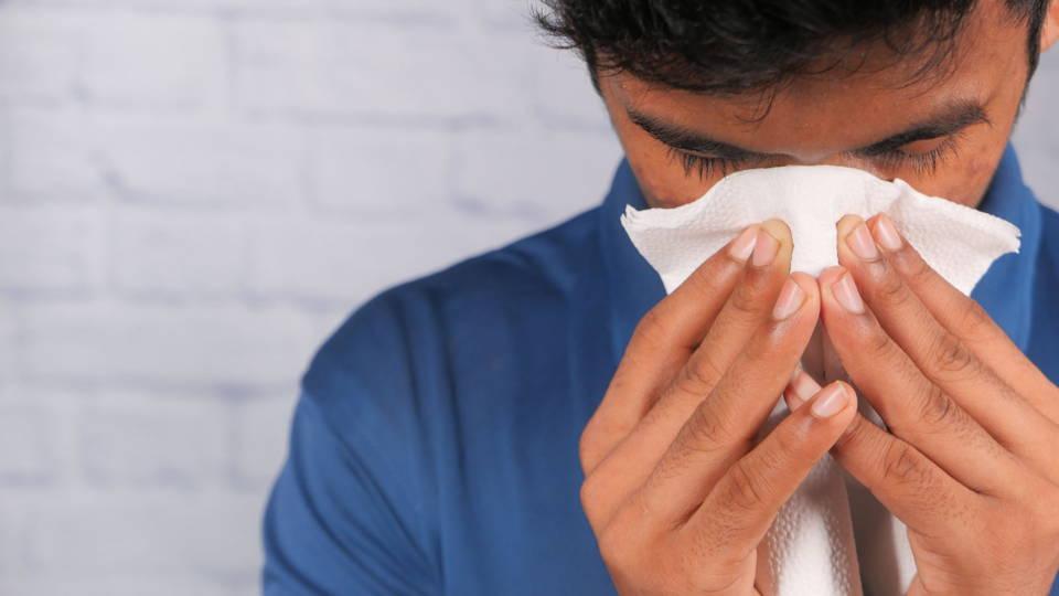 photo d'un homme qui tousse et qui est sujet à des allergies