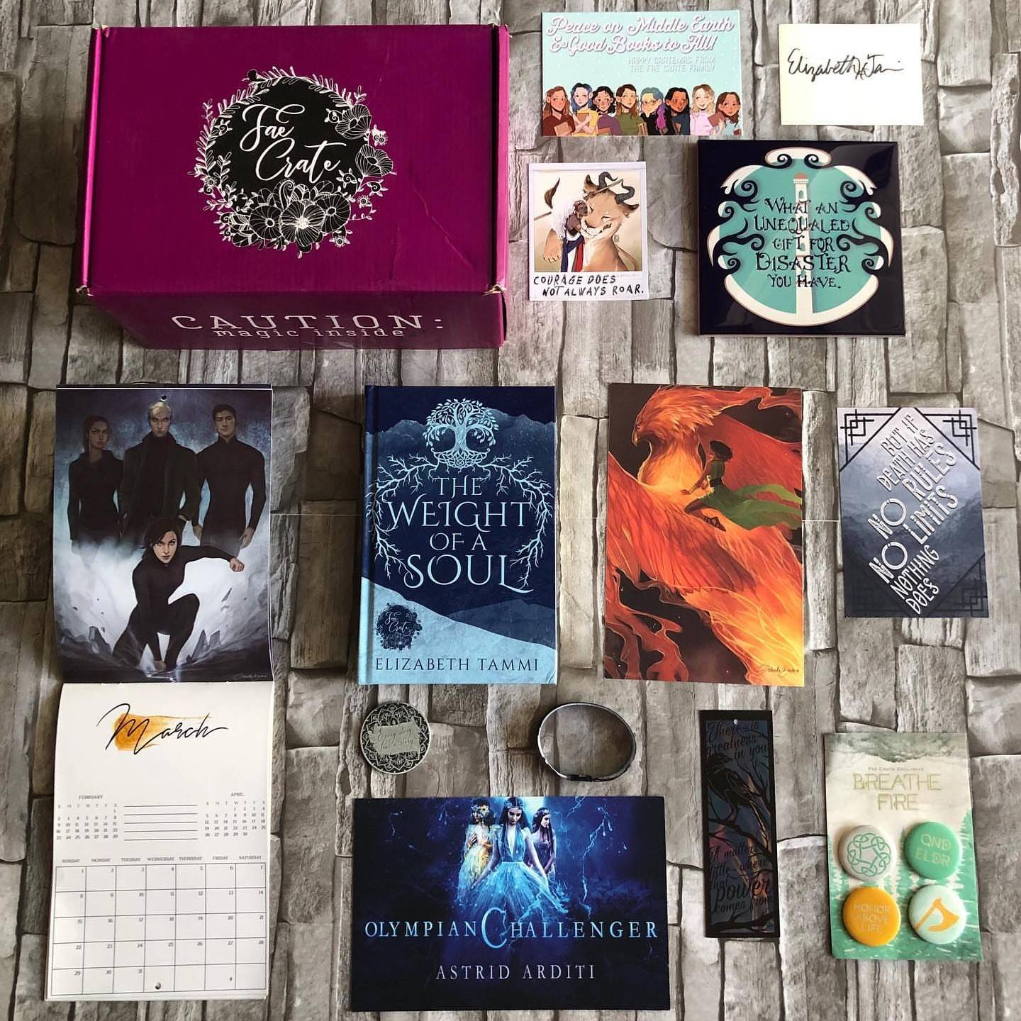 December 2019 Of Legends and Lore box theme included The Weight of a Soul by Elizabeth Tammi, Breathe Fire Button Set, Beyond a Darkened Shore Metallic Bookmark, 2020 Calendar, Uprooted Ceramic Trivet/Coaster, Stormdancer Wristband, The Wrath and the Down Collectors Coin, Crown of Feathers Theme Art, E-Book Download of Olympic Challenger by Astrid Arditi, Children of Blood and Bond Polaroid, and We Hunt the Flames Sweatshirt for Seelie and Solitary boxes only.