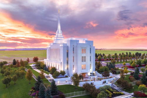 Aerial Rexburg Idaho Temple picture of green fields and pink clouds.