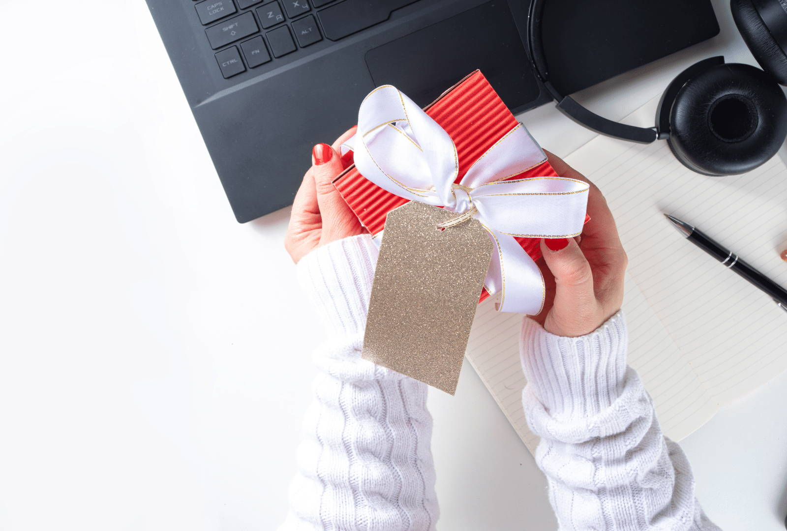 corporate client holding red gift box with a white ribbon. Computer and headphones in background on table.