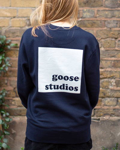 Back of woman wearing navy blue organic cotton sweatshirt with white printed logo from sustainable clothing brand Goose Studios