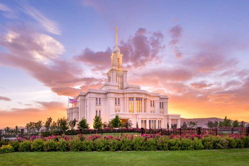 Colorful photo of the Payson Utah Temple against an orange sunset.