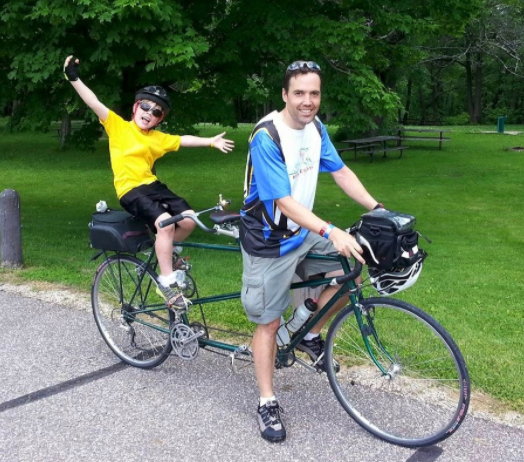 Photo of Steve and his son on a bike