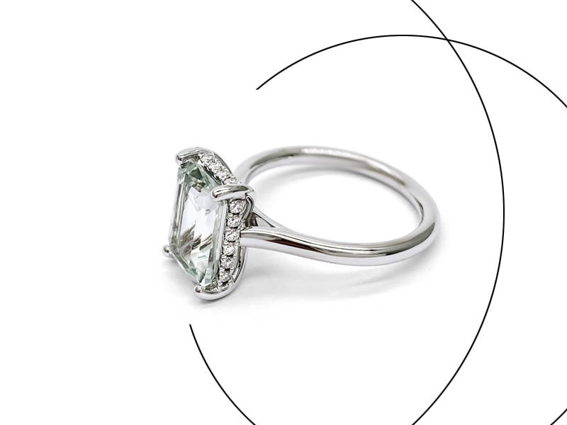Large princess diamond mounted on a white gold engagement ring with small diamonds on the outline of the main stone