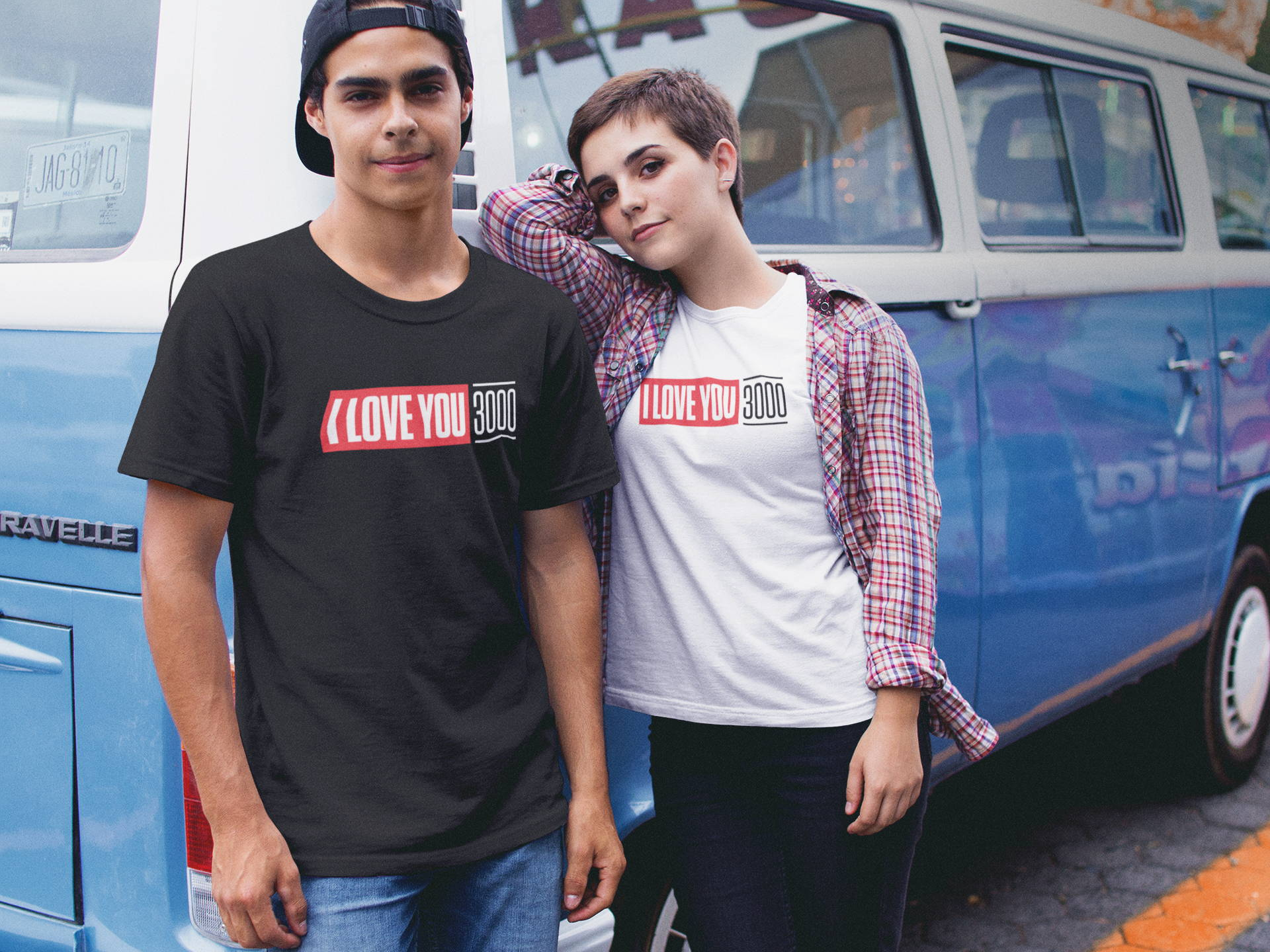 "Couple wearing different colored ""I Love You 3000"" t-shirts against a blue van."