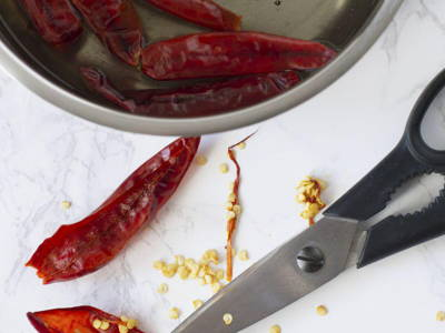 Soak dried chillies in room temperature water until they soften. Rinse well. Tip: To make the dish less spicy, boil the dried chillies instead of soaking them until soft. Then, remove the seeds and membranes of the dried chillies. Use rubber gloves when handling the dried chillies.