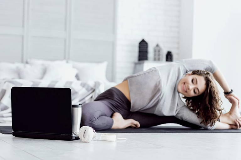 Women exercising at home while watching shows on her laptop
