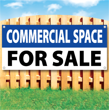 Wood fence displaying a banner saying 'COMMERCIAL SPACE' in white text on a blue background and 'FOR SALE' in black Text on White Background