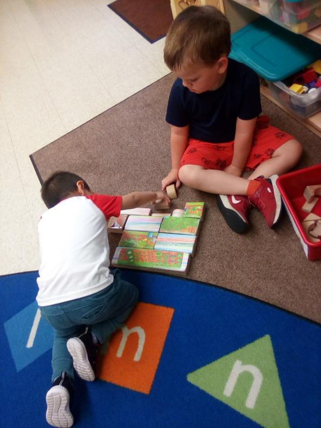 Two preschoolers sitting and putting blocks together that show scenes of a garden