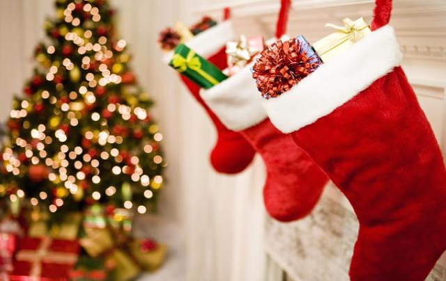 Christmas stocking hung on a mantle with decorated tree in background