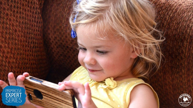 Little girl happily watches a video on a smartphone