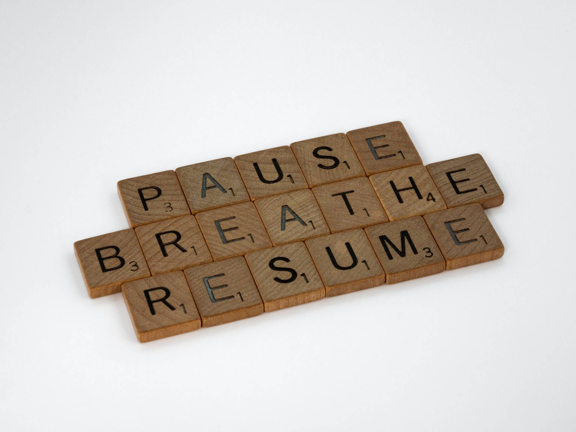 the words pause, breathe, resume written with scrabble letters