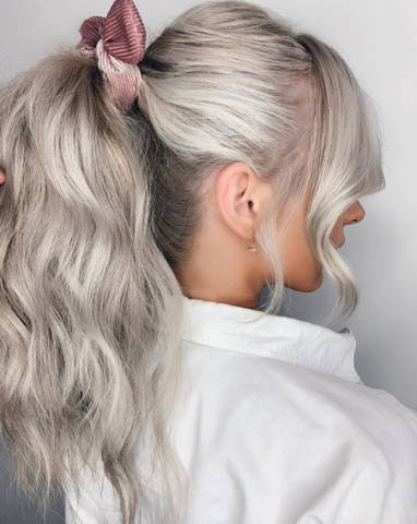 photo of a side view of a woman with platinum hair in a ponytail