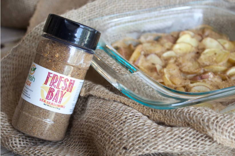 A bottle of FreshJax Fresh Bay Sea Seasoning next to a glass dish full of cooked scalloped potatoes.