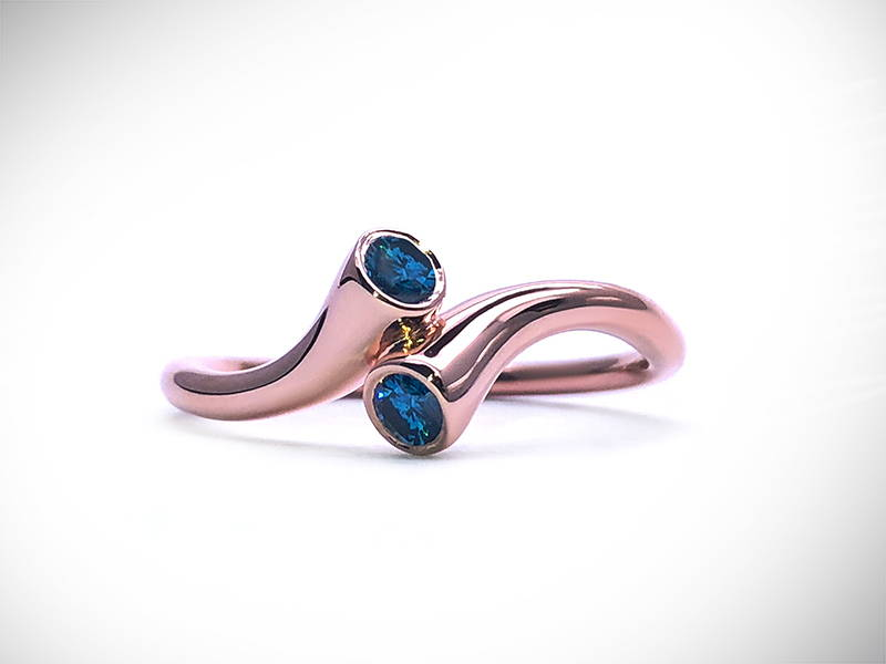 Pink gold twist ring with two blue diamonds