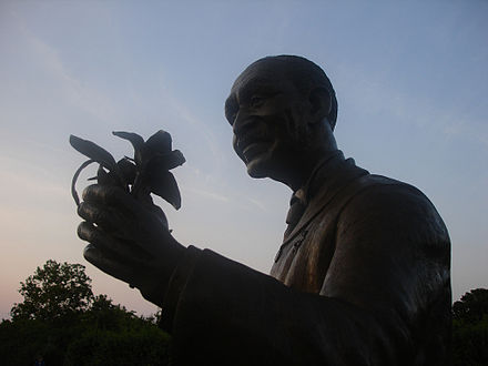 Silhouette of a statue of George holding a flower.