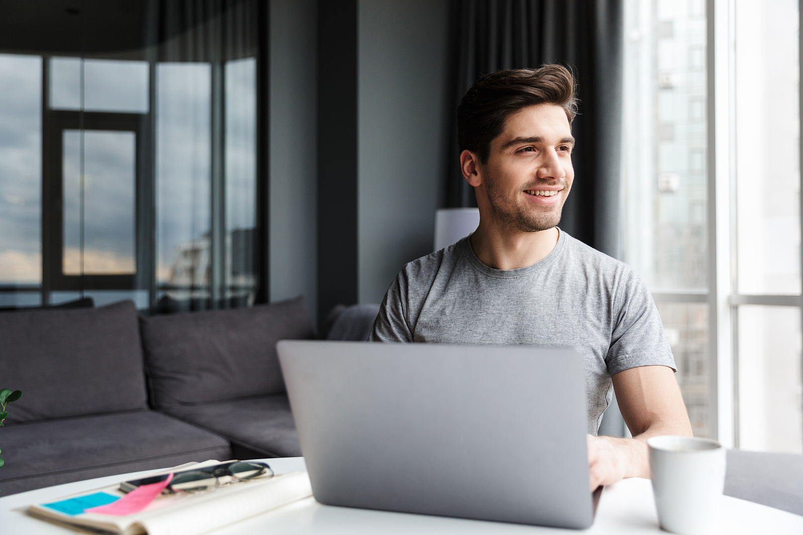 Image of attractive young white man looking out the window with a smile on his face, with a laptop in front of him.