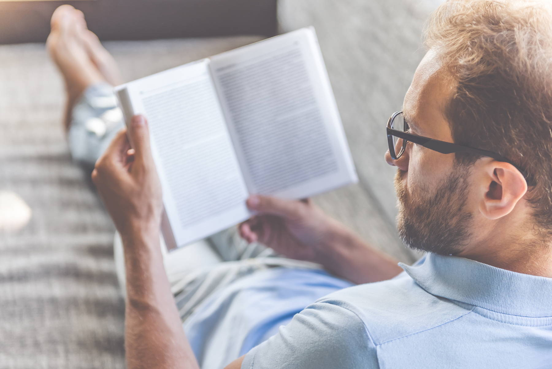 Man following tips to improve mood by relaxing with a book