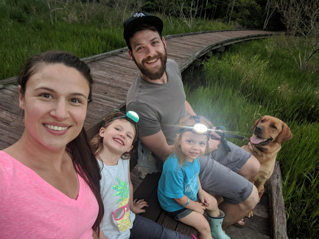 Family of 4 sitting by lake with dog