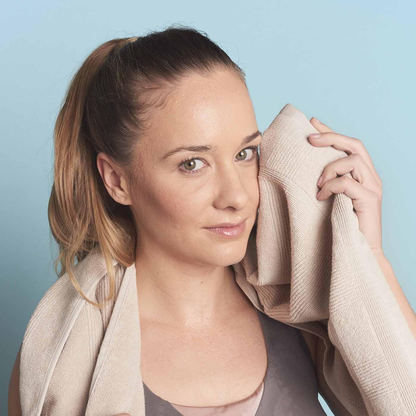 Schwitzende Frau trocknet mit einem Handtuch ihren Schweiß ab