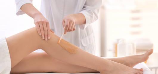 therapist waxing legs in beauty salon