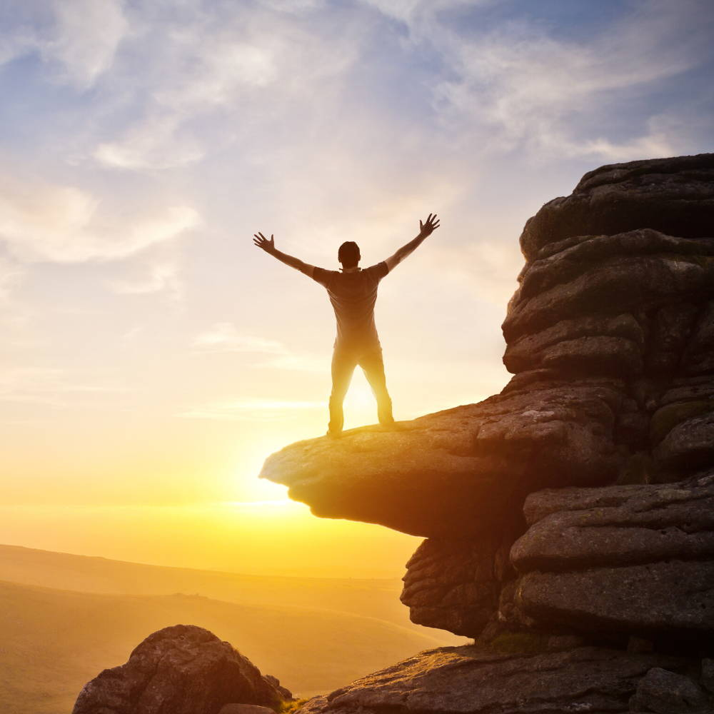 man with arms raised on top of a mountain cliff in front of the sunset