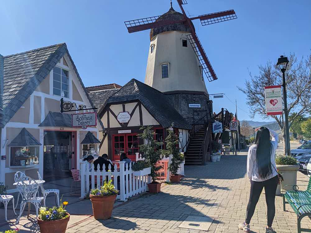 Woman looking at a windmill on a street in Solvang Santa Ynez Valley